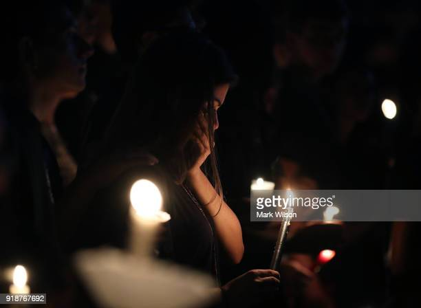 Students and family members attend a candlelight vigil for victims of the mass shooting at Marjory Stoneman Douglas High School yesterday at Pine...