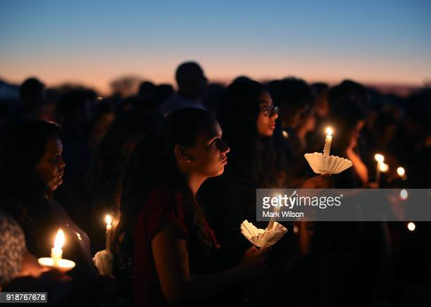 Students and family members hold candles during a vigil for victims of the mass shooting at Marjory Stoneman Douglas High School yesterday at Pine...