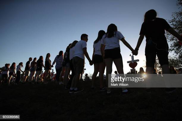 Students and family members holds hands around a makeshift memorial in front of Marjory Stoneman Douglas High School where 17 people were killed on...