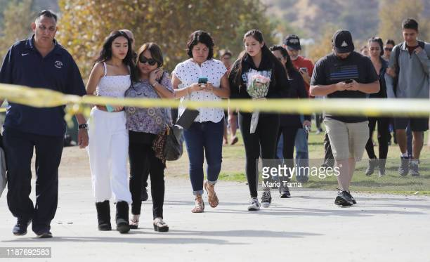Students and family members walk after being reunited at a park near Saugus High School after a shooting at the school left two students dead and...