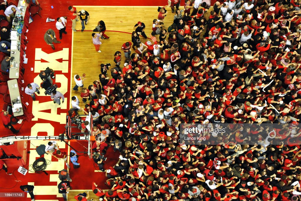 Students and fans of the North Carolina State Wolfpack rush onto the court following their victory over the #1 ranked Duke Blue Devils at PNC Arena on January 12, 2013 in Raleigh, North Carolina. NC State defeated Duke 84-76.