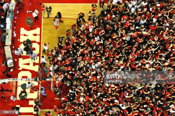 Students and fans of the North Carolina State Wolfpack rush onto the court following their victory over the ranked Duke Blue Devils at PNC Arena on...