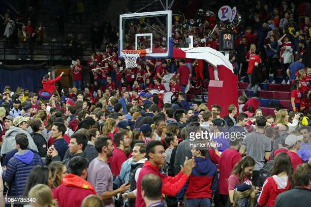 Students and fans of the Pennsylvania Quakers celebrate as they storm the court after winning a game against the Villanova Wildcats at The Palestra...