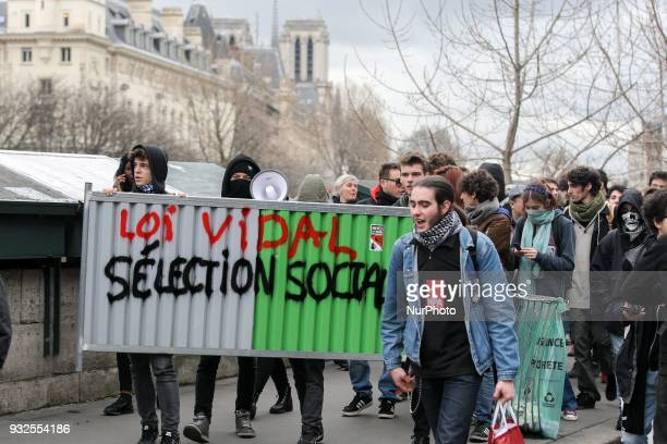 Students and high school students march behind a fence reading quotVidal law [in reference to French Minister of Higher Education Research and...