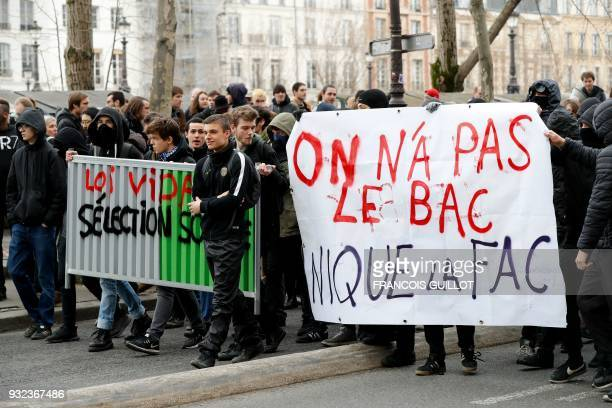 Students and high school students march behind a fence reading 'Vidal law [in reference to French Minister of Higher Education Research and...