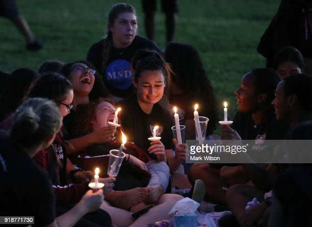 Students and hold candles during a vigil for victims of the mass shooting at Marjory Stoneman Douglas High School yesterday at Pine Trail Park on...