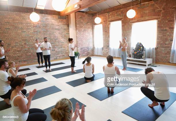 Students and instructor applauding in yoga class