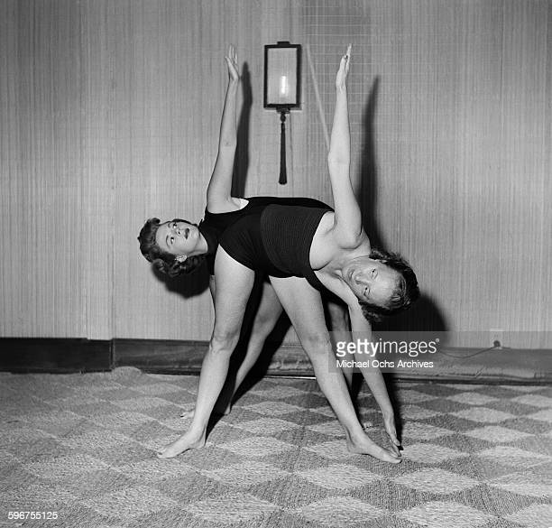 A students and instructor Indra Devi show a yoga pose at Indra Devi Yoga Studio in HollywoodCalifornia