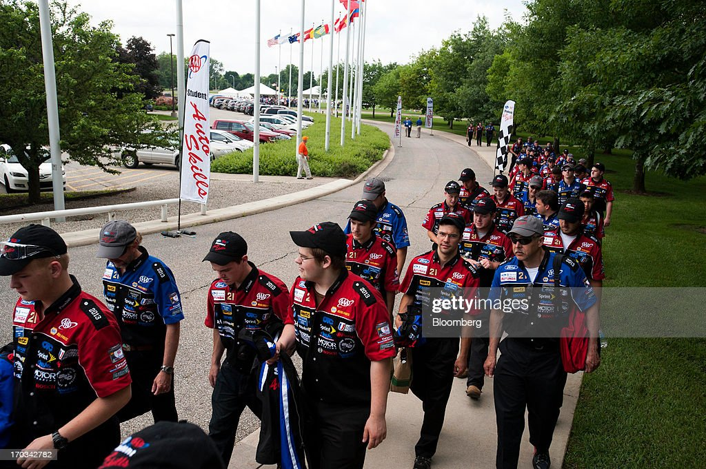 Students and instructors walk to the Ford Motor Co. World Headquarters for the awards ceremony during the National Finals of the Annual Ford/AAA Student Auto Skills Competition in Dearborn, Michigan, U.S., on Tuesday, June 11, 2013. Job openings in the U.S. fell in April, showing companies were waiting to assess the effects of higher taxes and reduced government spending before committing to bigger staff increases. Photographer: Ty Wright/Bloomberg via Getty Images