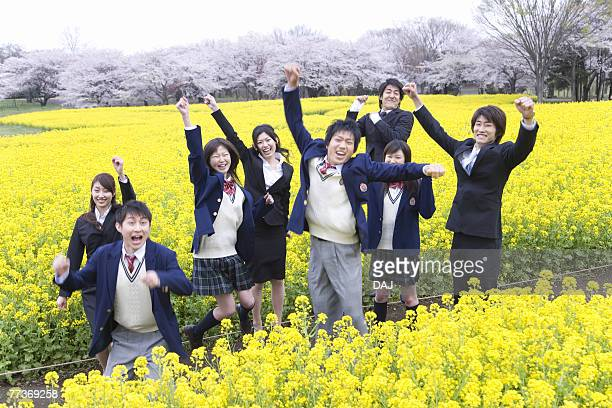 Students and New Business People Jumping In Rape Blossoms Field, Front View,