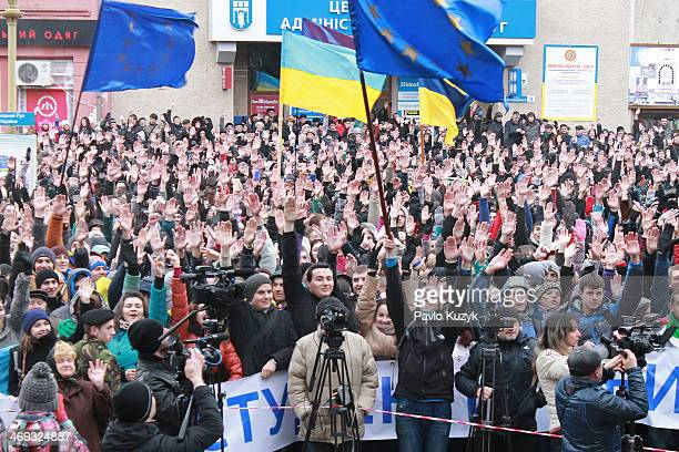 Students and other protesters show their approval of the resolution of the meeting in support of Euro-integration of Ukraine by raising their hands