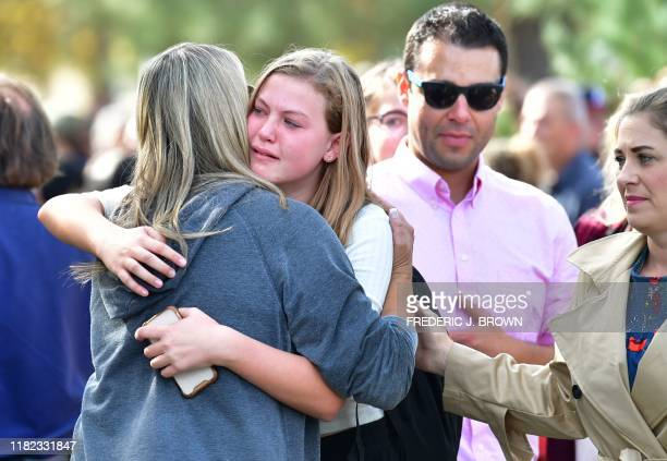 TOPSHOT Students and parents embrace after being picked up at Central Park after a shooting at Saugus High School in Santa Clarita California on...