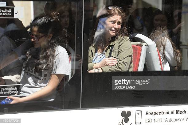 Students and parents leave the Joan Fuster Institute in a bus in Barcelona on April 20 2015 after a student allegedley broke into the school armed...