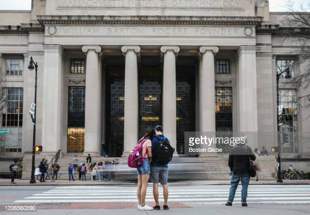 Students and pedestrians walk though MIT's campus in Kendall Square in Cambridge MA on March 10 2020 Some colleges have moved all classes online amid...