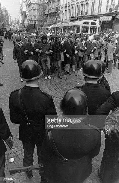 Students and police facing each other in a Paris street during the student riots
