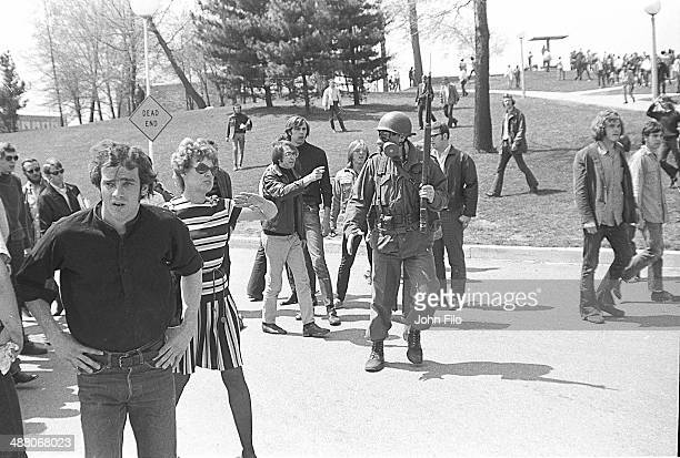 Students and protesters stand around a lone Ohio National Guard soldier in a gas mask and with a rifle in his hands during an antiwar demonstration...