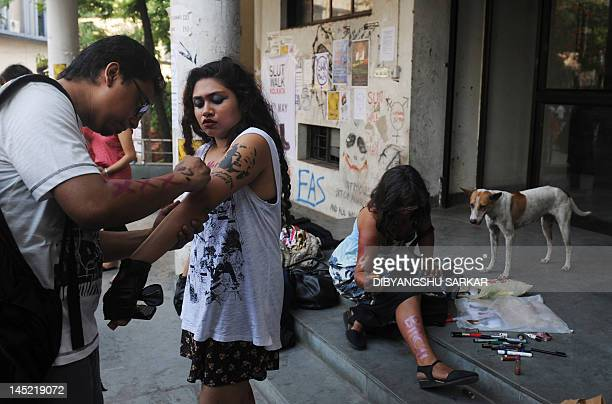Students and social activists put on makeup prior to particiapting in a Slut Walk in Kolkata on May 24 2012 Hundreds of supporters particiapted in...