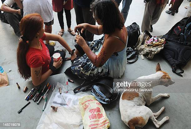 Students and social activists put on makeup prior to particiapting in a 'Slut Walk' in Kolkata on May 24 2012 Hundreds of supporters particiapted in...