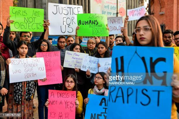 Students and social workers hold placards during a protest seeking for justice for the rape case of a 27-year-old veterinary doctor from Hyderabad,...