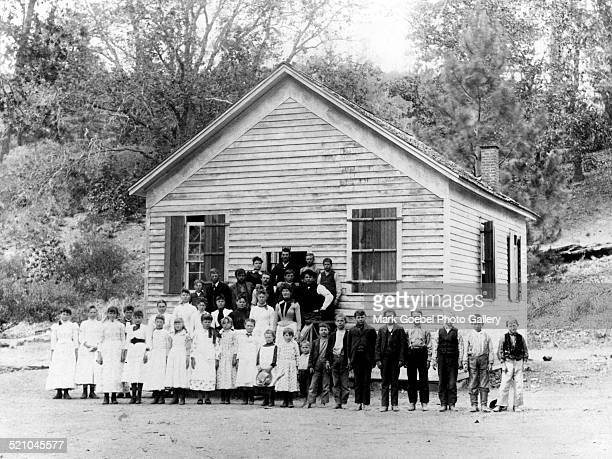 Students and teacher in front of one room school house mid 1910s