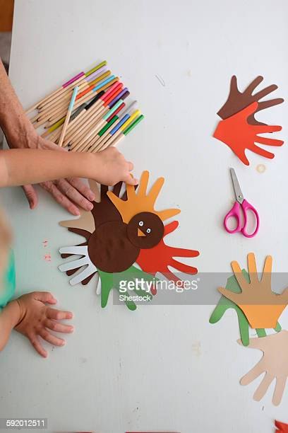 students and teacher making thanksgiving turkey crafts in classroom - turkey feathers stock photos and pictures