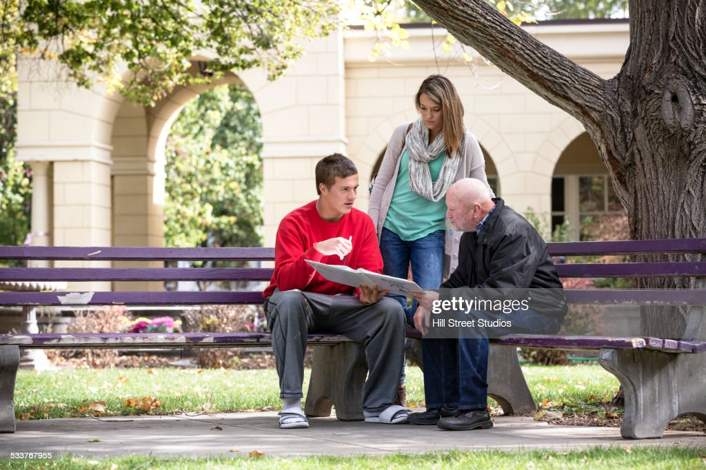 Students and teacher talking on park benches : Foto stock