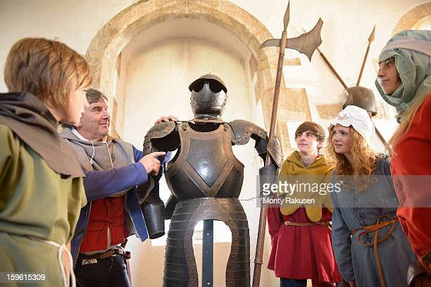 students and teacher with armour, bolton castle, 14th century grade 1 listed building, scheduled ancient monument - history stock-fotos und bilder