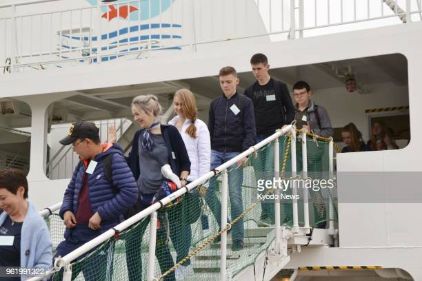 Students and teachers from disputed islands off Hokkaido arrive at Nemuro port on Japan's northernmost main island on May 24 under a visafree...