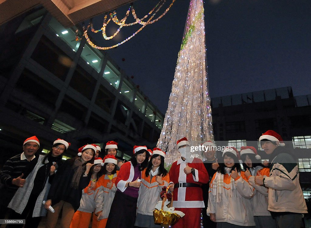 Students and teachers pose for photos in front of a Christmas tree in Taipei on December 24, 2012. The tree was made by students and teachers of Taipei Municipal YuCheng Senior High School using environmental resource recycling materials to mark Christmas. AFP PHOTO / Mandy CHENG
