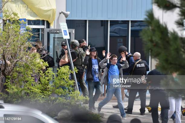 Students and teachers raise their arms as the exit the scene of a shooting in which at least seven students were injured at the STEM School Highlands...