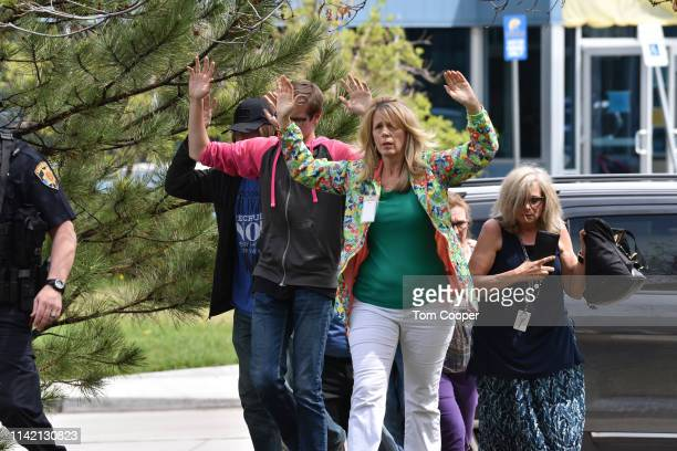 Students and teachers raise their arms as they exit the scene of a shooting in which at least seven students were injured at the STEM School...
