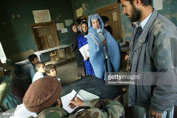 Students and teachers wait for documents to be signed by the administrator at Amir Dost Mohammed Khan elementary school April 1 2002 in Kabul Some...