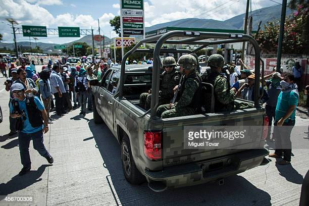 Students and the relatives of missing students try to stop a military convoy to block the highway on October 05 2014 in Chilpancingo Mexico...