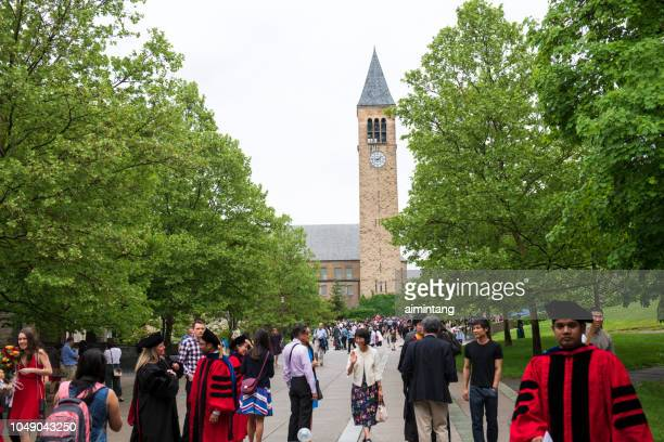 Students and their family members gathered by Jennie McGraw Tower in the campus of Cornell University on commencement day