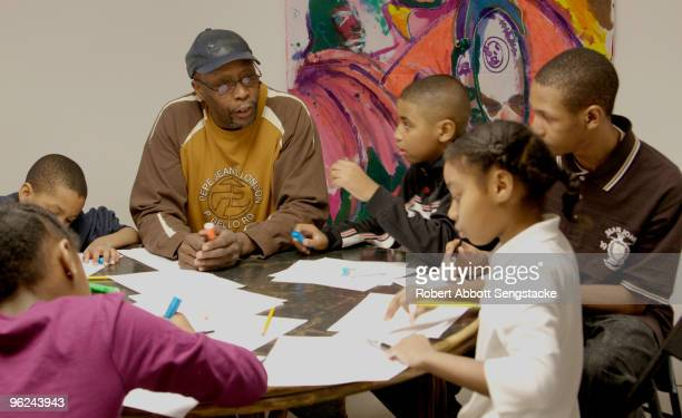 Students and volunteer mentors gather around a table while participating in a RALD Institute program Chicago IL ca2000s The institute run by...