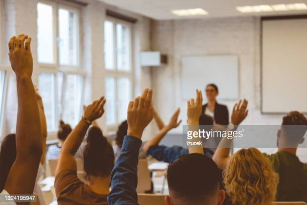 students answering to teacher during lecture - izusek stock pictures, royalty-free photos & images