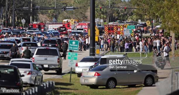 Students are brought across Coral Springs Drive from the the campus of Stoneman Douglas High School in Parkland Fla after a shooting on Wednesday Feb...