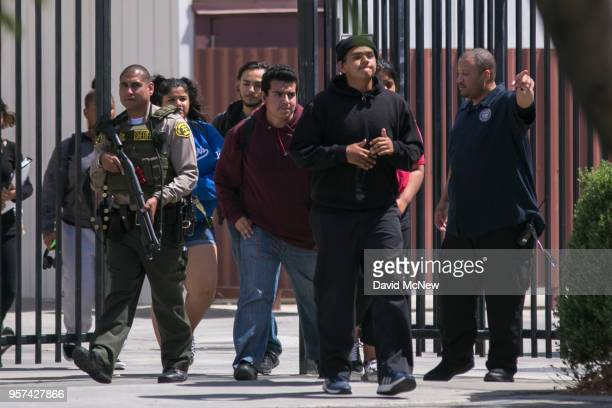 Students are escorted from campus to be reunited with friends and family after a shooting at Highland High School on May 11 2018 in Palmdale...