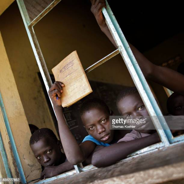 Students are looking out of an open window of a school at Rhino Refugee Camp Settlement in northern Uganda Here children of local people and refugees...