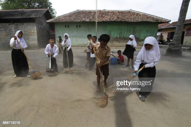 Students are seen cleaning the dusty yard in front of their classroom after school time in Sadah State Elementary School located in Ciruas...