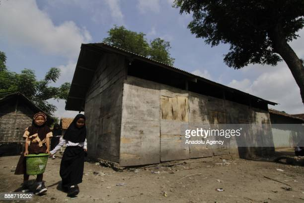 Students are seen playing and cleaning the dusty yard in front of their classroom after school time in Sadah State Elementary School located in...