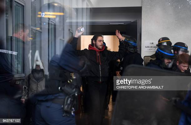 TOPSHOT Students are seen through a window at Nanterre College in Nanterre on April 9 as they are escorted from a building by gendarmes during an...