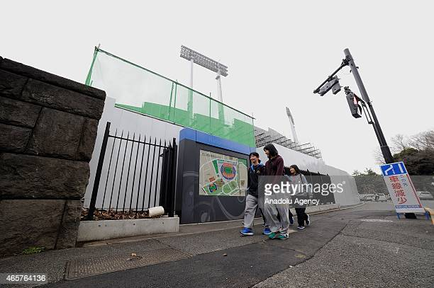 Students are seen walking near the National Stadium in Tokyo Japan on March 10 2015 The old National olympic stadium of Tokyo Sendagaya district...