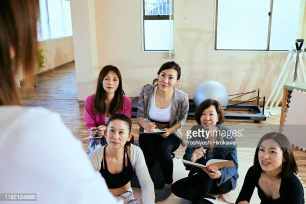 students are seriously listening to women's teachers in the fitness studio classroom - endast vuxna bildbanksfoton och bilder