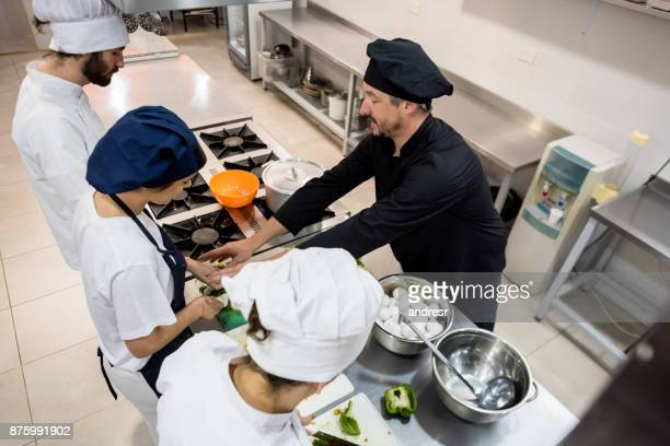 students at a cooking class with a professional chef - food and drink stock pictures, royalty-free photos & images
