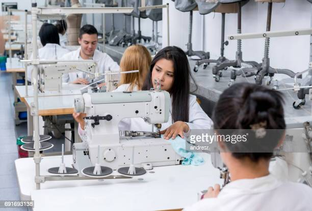 Students at a fashion school sewing on machines