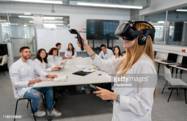 students at college doing an experiment watching a student while using virtual reality headset and joysticks - cyberspace stock pictures, royalty-free photos & images