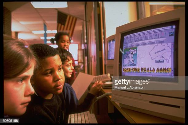 Students at computer traveling to Australia on Internet at Horace Mann Elementary School 1 among half of public schools w access to Internet