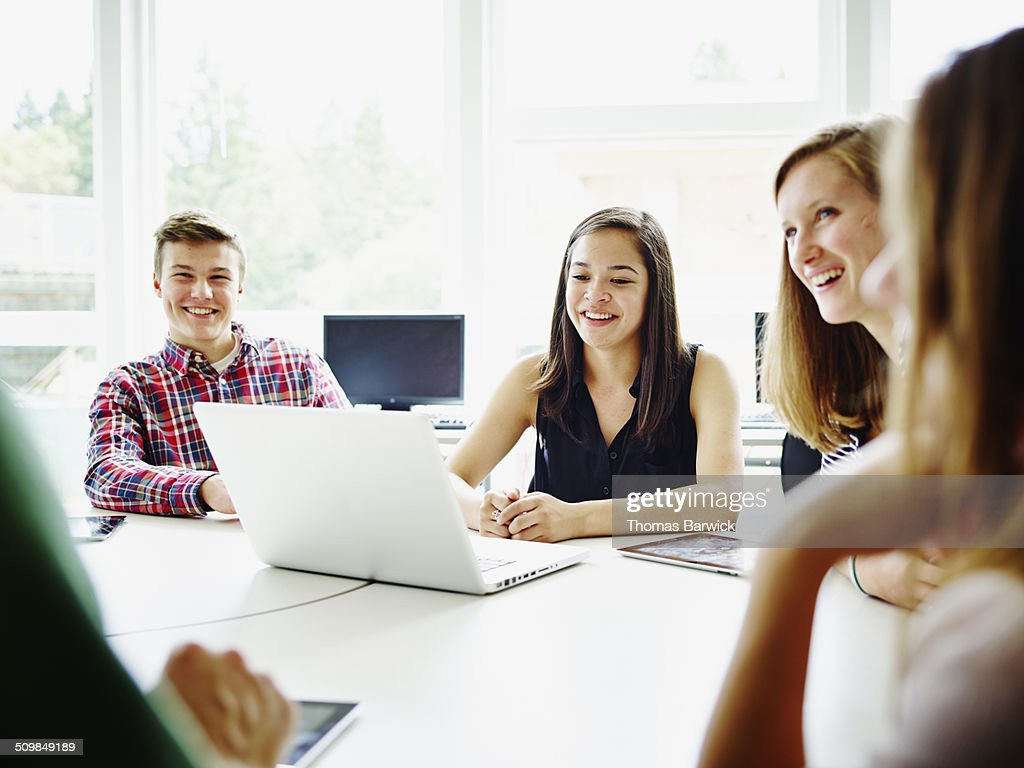 Students at desk in classroom listening to teacher : Stock Photo