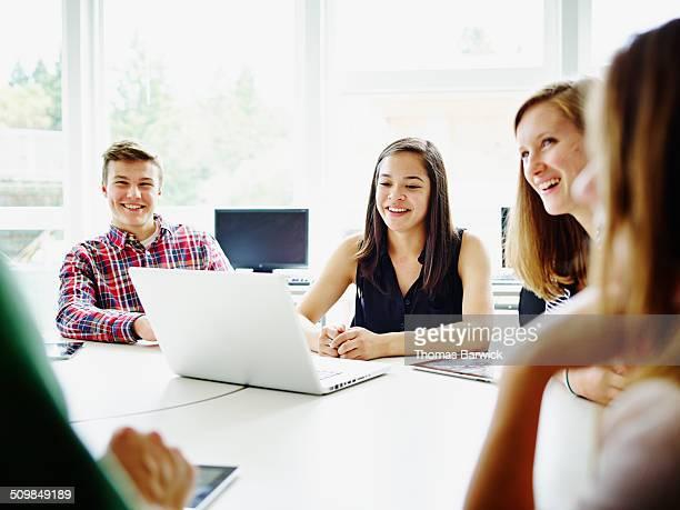 students at desk in classroom listening to teacher - schüler stock-fotos und bilder